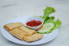 Fried popiah. Served with chili sauce and decorated with a slice of cucumber and salad leaf royalty free stock photos