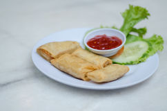 Fried popiah. Served with chili sauce and decorated with a slice of cucumber and salad leaf Royalty Free Stock Images