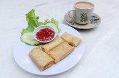 Fried popiah. Served with chili sauce and decorated with a slice of cucumber and salad leaf Stock Image