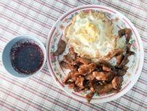 Fried Pork avec le poivre d'ail sur la sauce à oeuf au plat et à Chili Pepper Spicy de riz plongeant les nourritures thaïlandaise image stock