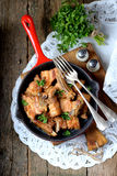 Fried pork belly in a cast-iron frying pan with onion, garlic and soy sauce. Stock Images