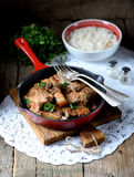 Fried pork belly in a cast-iron frying pan with onion, garlic and soy sauce. Royalty Free Stock Photography