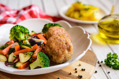 Fried pork burgers served with steamed vegetable. Fried pork burgers served with steamed zucchini, broccoli, bell pepper, red onion and garlic Stock Images