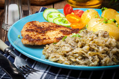 Fried pork chop, baked potatoes and fried young cabbage. Stock Images