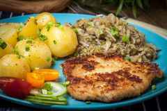 Fried pork chop, baked potatoes and fried young cabbage. Stock Photos