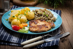 Fried pork chop, baked potatoes and fried young cabbage. Royalty Free Stock Images