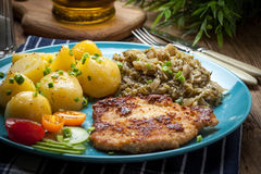 Fried pork chop, baked potatoes and fried young cabbage. Stock Photography