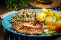 Fried pork chop, baked potatoes and fried young cabbage. Royalty Free Stock Photography