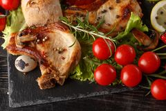 Fried pork chop on a black plate with spices, herbs and tomatoes stock photos