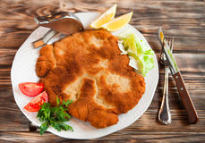 Fried pork chop coat in breadcrumbs with lemon slise and vegetab Stock Image