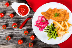 Fried pork chop with french fries, green bean and salad Stock Photos