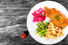 Fried pork chop with french fries, green bean and salad Royalty Free Stock Photos