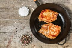 Fried pork chops in a pan with pepper and salt. The view from the top. Copy-space. Fried pork chop in a pan with pepper and salt on a table of old boards Royalty Free Stock Photography