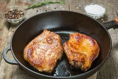 Fried pork chops in a pan with pepper and salt. The view from the top. Copy-space. Fried pork chop in a pan with pepper and salt on a table of old boards Royalty Free Stock Image