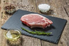 Raw pork chop with pepper and salt on a stone serving Board. Fried pork chop in a pan with pepper and salt on a table of old wooden boards Stock Photos