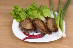 Fried pork chop, and vegetable. Grilled pork chop on a plate with onions and peppers lettuce Royalty Free Stock Images