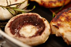 Fried pork chops and champignon mushrooms in the frying pan Stock Photography