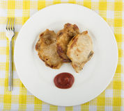 Fried pork cutlet, tomato sauce in plate on tablecloth Stock Photos