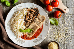Fried pork cutlets with rice, tomato and mushrooms Royalty Free Stock Photos