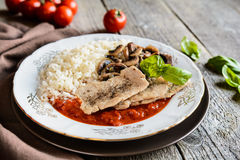 Fried pork cutlets with rice, tomato and mushrooms Royalty Free Stock Photo