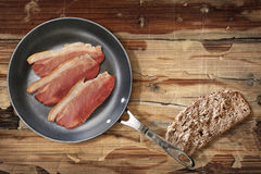 Prosciutto Rashers In Teflon Frying Pan And Slice Of Brown Bread Set On Old Cracked Flaky Wooden Garden Table Stock Photo