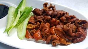 Fried pork intestines serve withvegetable. Fried pork intestines serve with vegetable Royalty Free Stock Photo