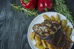 Fried pork knuckle with potatoes served on a white plate. Decorated with fresh Bulgarian pepper, rosemary. Dark wooden background royalty free stock image
