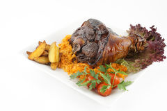 Fried pork knuckle with potatoes and tomato. Isolated Royalty Free Stock Photography