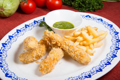 Fried pork meat with french fries. And pesto sauce Royalty Free Stock Image
