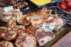 Fried pork meat. Freshly cooked pork meat and specialties for sale at outdoor fair Royalty Free Stock Photo