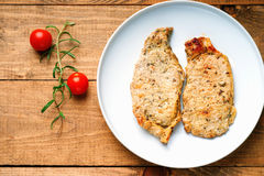 Fried pork meat and tomatoes. On a wooden background Royalty Free Stock Photos