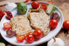 Fried pork meat and vegetables. On a white dish Royalty Free Stock Photo