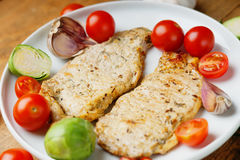 Fried pork meat and vegetables. On a white dish Royalty Free Stock Images