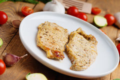 Fried pork meat and vegetables. On a wooden background Stock Photography