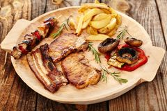 Fried pork meat with wedges potatoes  and grilled vegetables. Closeup of fried pork meat with wedges potatoes and grilled vegetables on a wooden plate, decorated Royalty Free Stock Photography