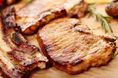 Fried pork meat on a wooden board. Closeup of  spiced fried pork meat decorated with rosemary on a wooden board, selective focus Royalty Free Stock Photo