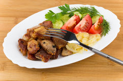 Fried pork and onions with tomatoes, cucumbers and greens Royalty Free Stock Photography