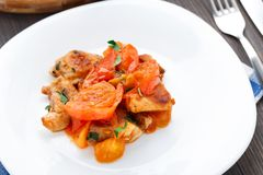Fried pork with pan-roasted tomatoes Stock Photography