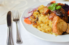 Fried pork or piglet served with roasted potatoes and lilac cabbage Stock Photography