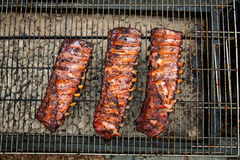 Fried pork ribs with barbecue sauce on outdoor grill Stock Photos