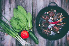 Fried pork ribs with a black frying pan Stock Image