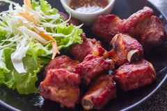 Fried pork. Ribs with salad on black dish Royalty Free Stock Photos