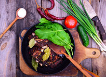Fried pork ribs in spices on a black cast-iron frying pan Royalty Free Stock Photos