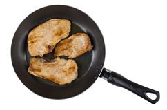 Fried pork schnitzel in frying pan isolated on white background Stock Images