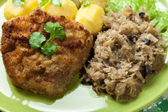 Fried pork schnitzel served with boiled potatoes and fried sauer Royalty Free Stock Images