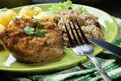 Fried pork schnitzel served with boiled potatoes and fried sauer Stock Image