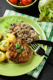 Fried pork schnitzel served with boiled potatoes and fried sauer Royalty Free Stock Photo