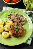 Fried pork schnitzel served with boiled potatoes and fried sauer Stock Images