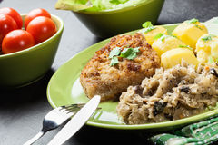 Fried pork schnitzel served with boiled potatoes and fried sauer Royalty Free Stock Image