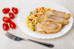 Fried pork schnitzel with vegetable mix in plate, cherry tomatoe Stock Images